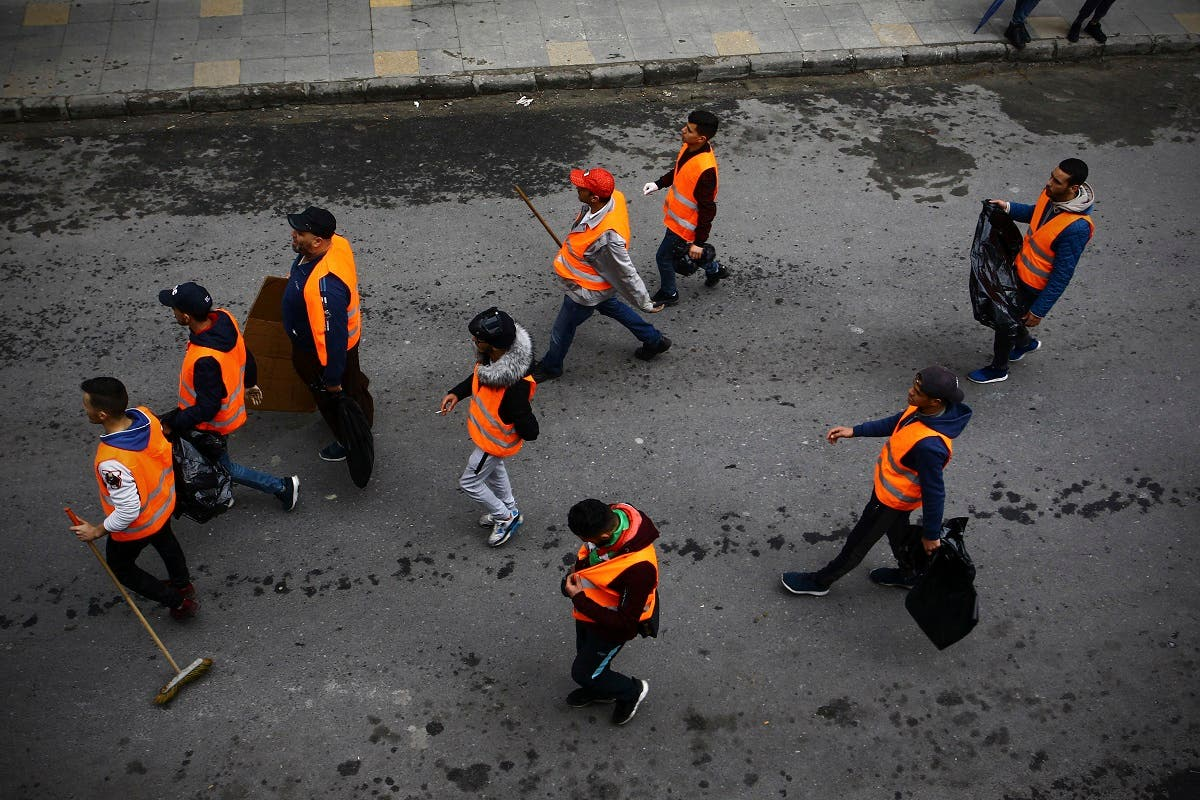 Algerian protesters cleaning up. (AP)
