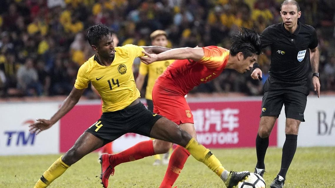 Malaysia's Mohamed Syamer Kutty Abba (L) fights for the ball with China's Zhang Yuning during the Tokyo 2020 Olympic Games men's Asian qualifier football match between China and Malaysia in Shah Alam on March 26, 2019. (AFP)