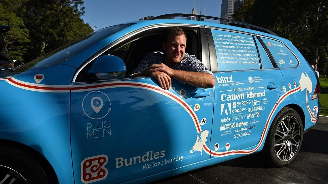 """Dutch driver Wiebe Wakker sits in his retrofitted station wagon nicknamed """"The Blue Bandit"""" after completing a round-an-world trip in an electric car in Sydney on April 7, 2019. (AFP)"""
