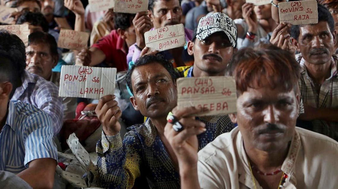 Released Indian fishermen display their name tags while waiting for train at a railway station to leave for their homeland, in Karachi, Pakistan, Sunday, April 7, 2019. (AP)