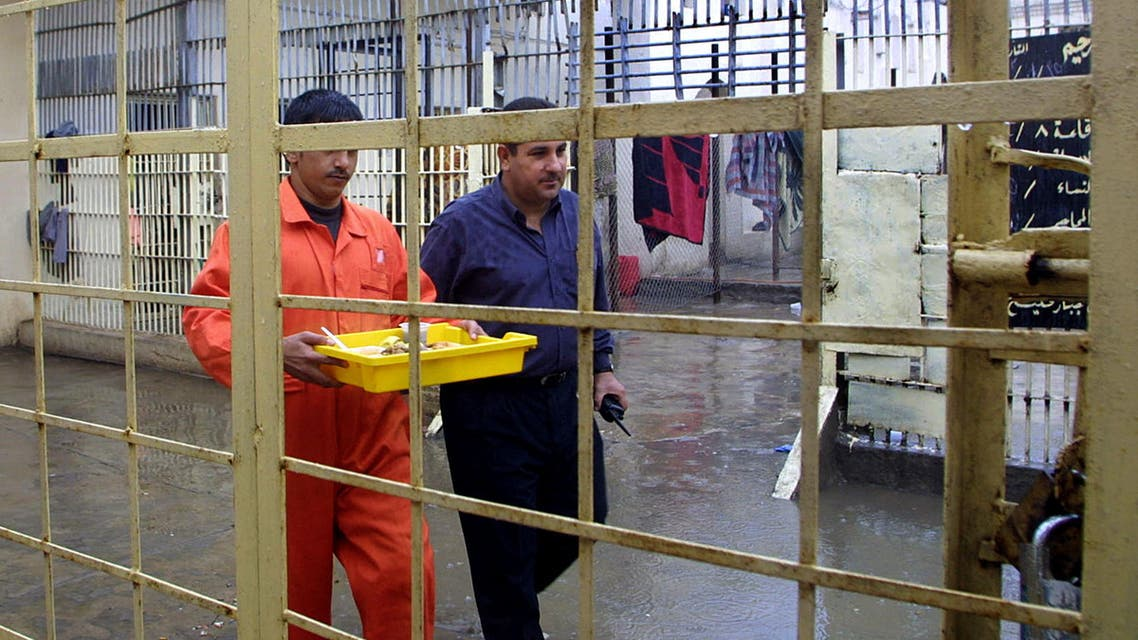 An Iraqi security man escorts a prisoner in a prison in Basra on 16 November 2005. (File photo: AFP)