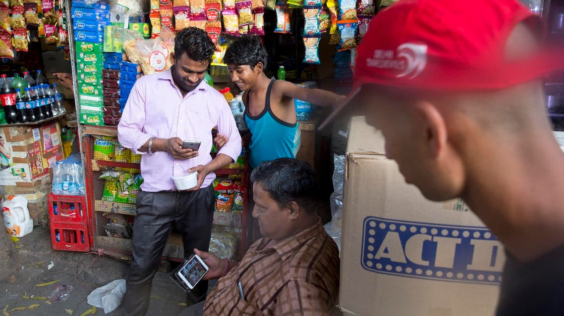 Ram Shankar Rai watches election campaign advertisements on his mobile phone outside his shop in New Delhi April 8, 2019. (AP)