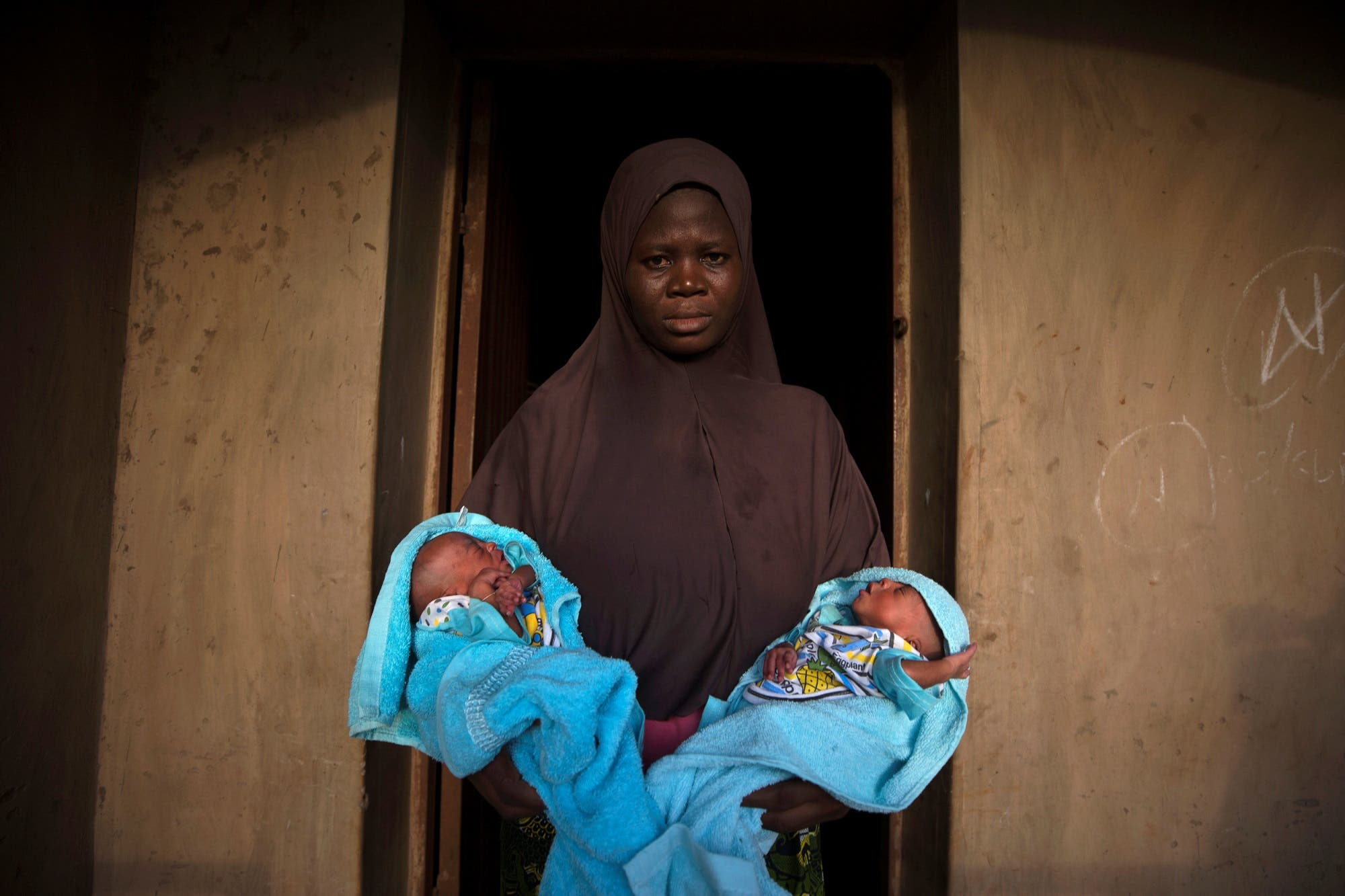 A Muslim woman carries her four-day-old male twins outside her home in Igbo Ora, Oyo State, Nigeria on April 3, 2019. (Reuters)