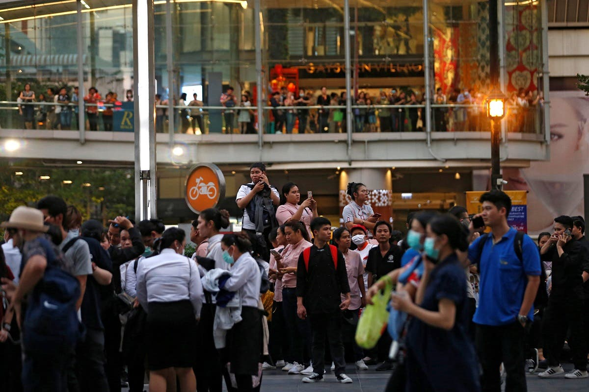 People stand outside the Central World Complex after it was evacuated due to a fire, in Bangkok, Thailand, on April 10, 2019. (Reuters)