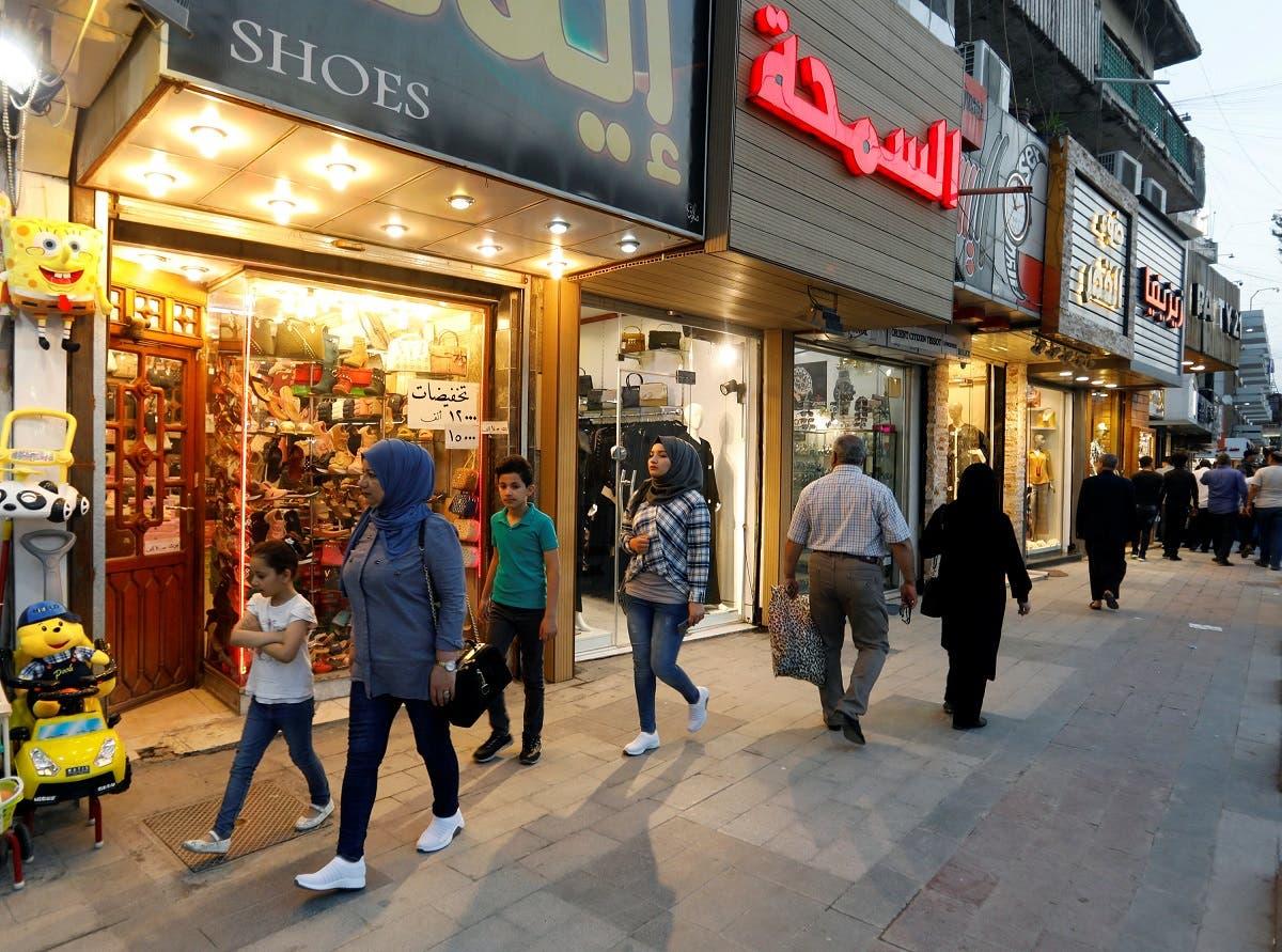 Iraqi people walk past shops in Baghdad, Iraq. (Reuters)