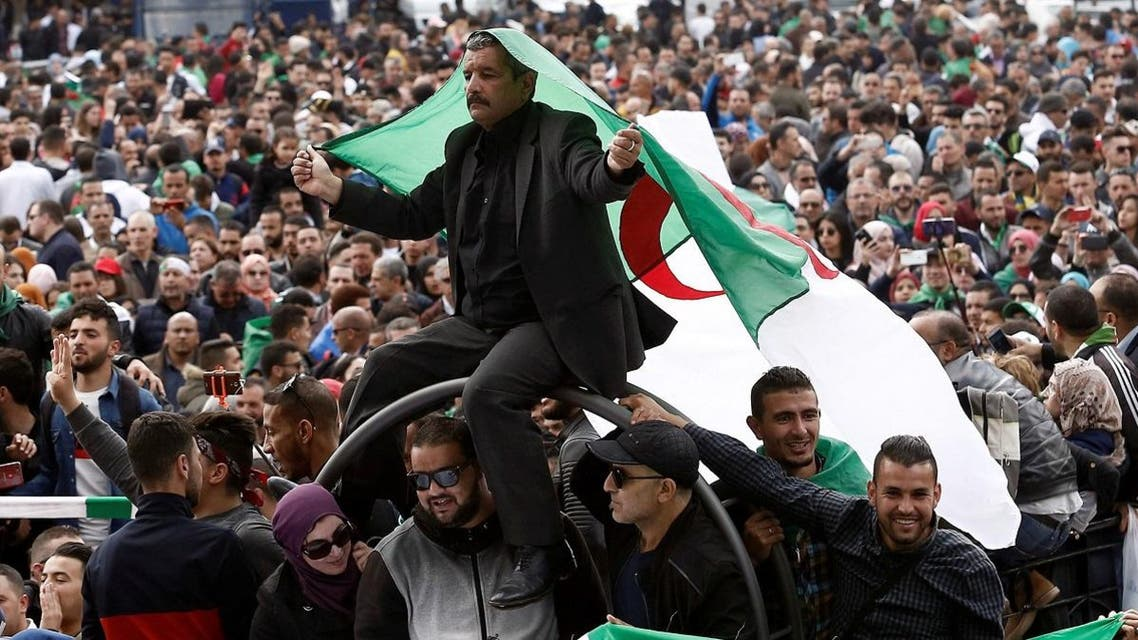 A man carries a national flag during a protest against the appointment of interim president, Abdelkader Bensalah. (Reuters)