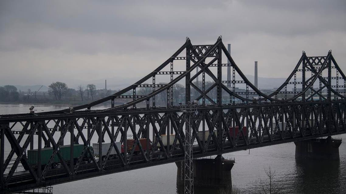 trucks crossing the Friendship Bridge from the Chinese border city of Dandong to North Korea's Sinuiju over the Yalu river. (AFP)