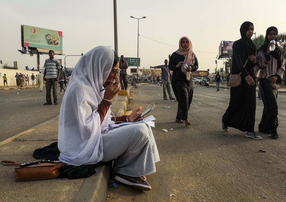 Alaa Salah, a Sudanese woman propelled to internet fame earlier this week after clips went viral of her leading powerful protest chants against President Omar al-Bashir, speaks on the phone as she sits during a demonstration in front of the military headquarters in the capital Khartoum on April 10, 2019. (AFP)