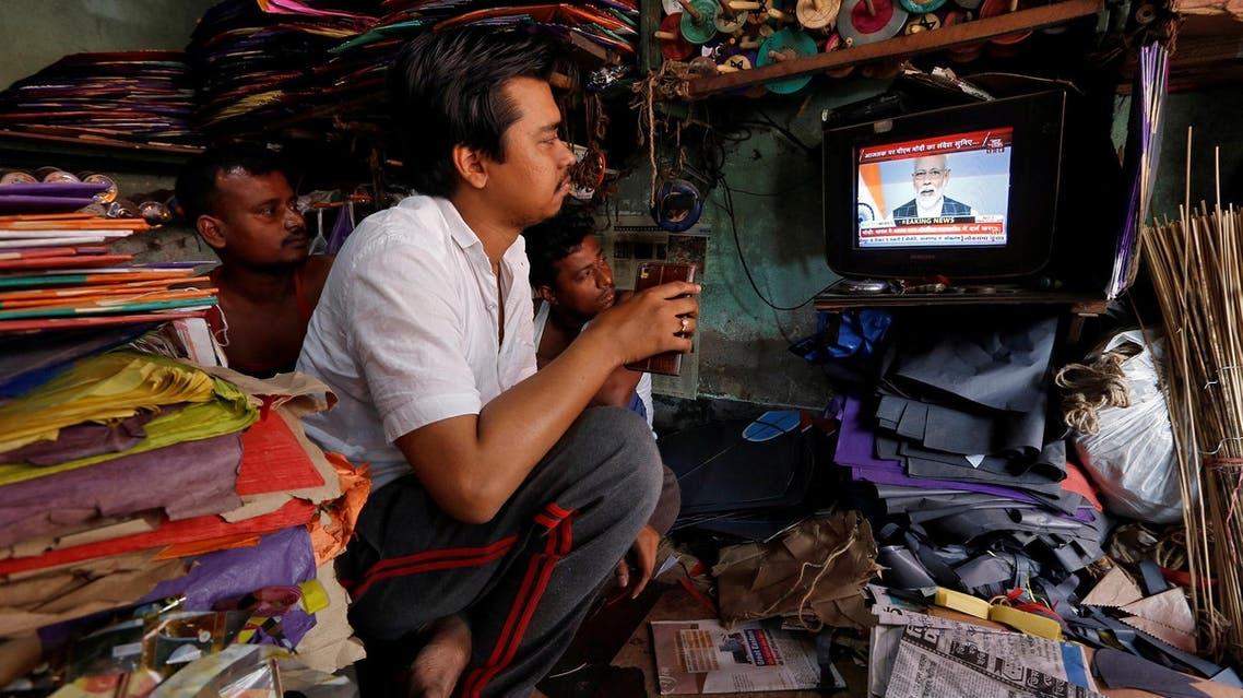 Men watch Narendra Modi on a TV screen inside their shop in Kolkata on March 27, 2019. (Reuters)