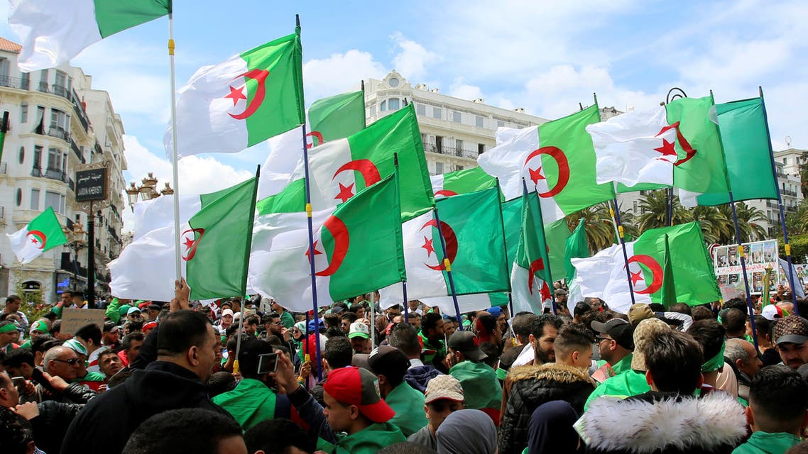 People carry national flags during a protest seeking the departure of the ruling elite, as the country prepares for presidential election in Algiers, Algeria April 12, 2019. REUTERS/Ramzi Boudina