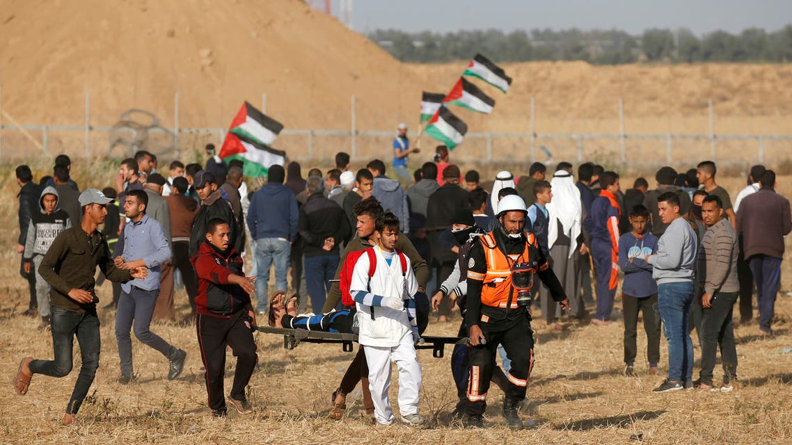 Palestinian paramedics carry an injured protester during a demonstration near the border between Israel and Khan Yunis in the southern Gaza Strip, on April 12, 2019.