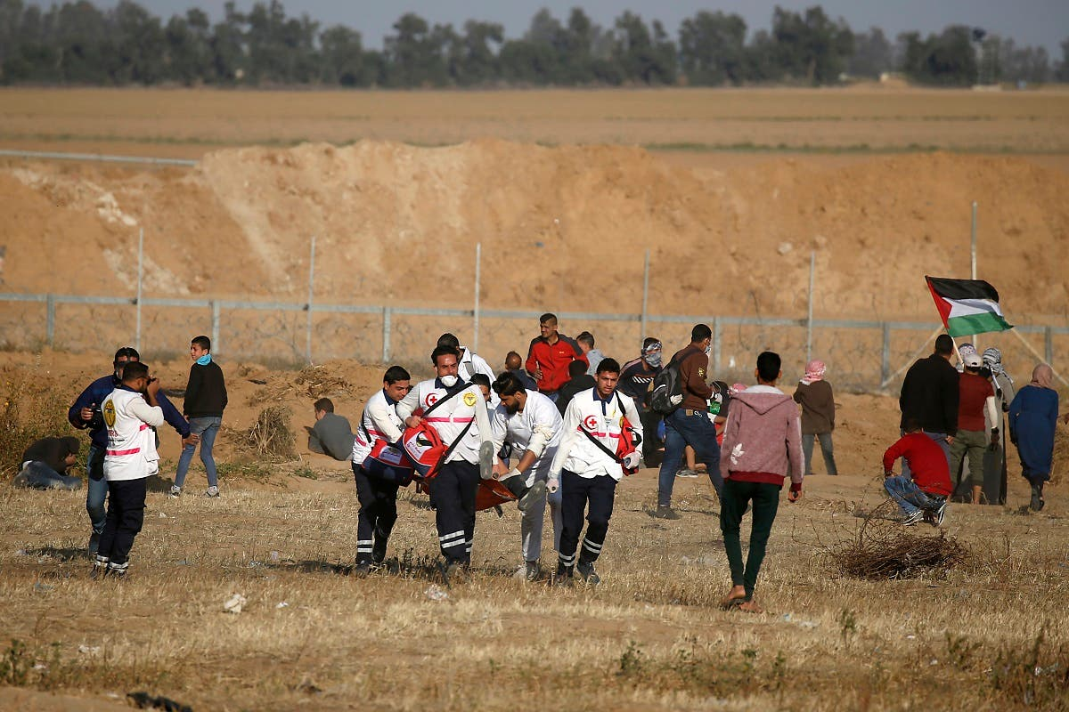 Palestinian paramedics carry an injured protester during a demonstration near the border between Israel and Khan Yunis in the southern Gaza Strip, on April 12, 2019. (AFP)