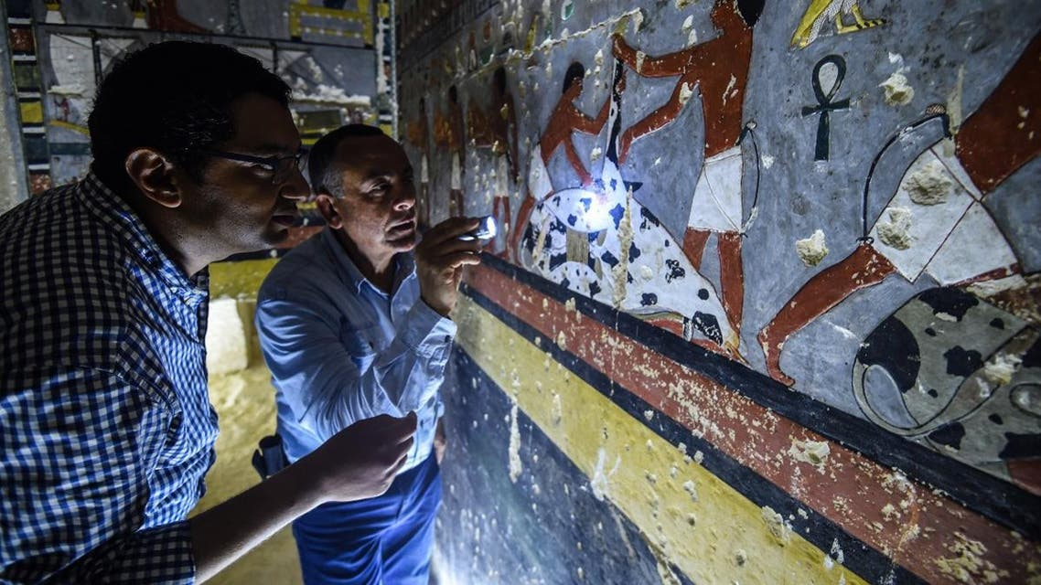 """Mohamed Mujahid (L), head of the Egyptian mission which discovered the tomb of the ancient Egyptian nobleman """"Khuwy"""" dating back to the 5th dynasty, inspects the tomb's walls inside at the Saqqara necropolis. (AFP)"""