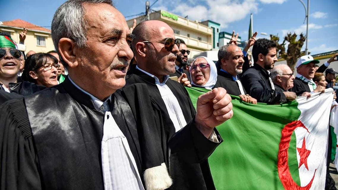 Algerian lawyers and judges chant slogans and raise a national flag as they gather for a demonstration for the independence of the judiciary outside the Justice Ministry headquarters in the capital Algiers. (AFP)