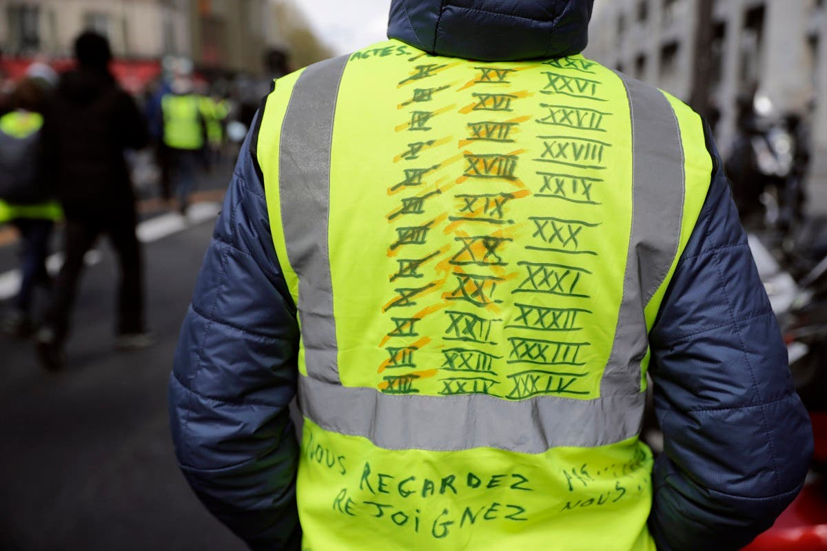A demonstrator wearing a yellow vest noted with all the attended acts and the future ones as he and thousands march on April 13, 2019 in Paris. (AFP)