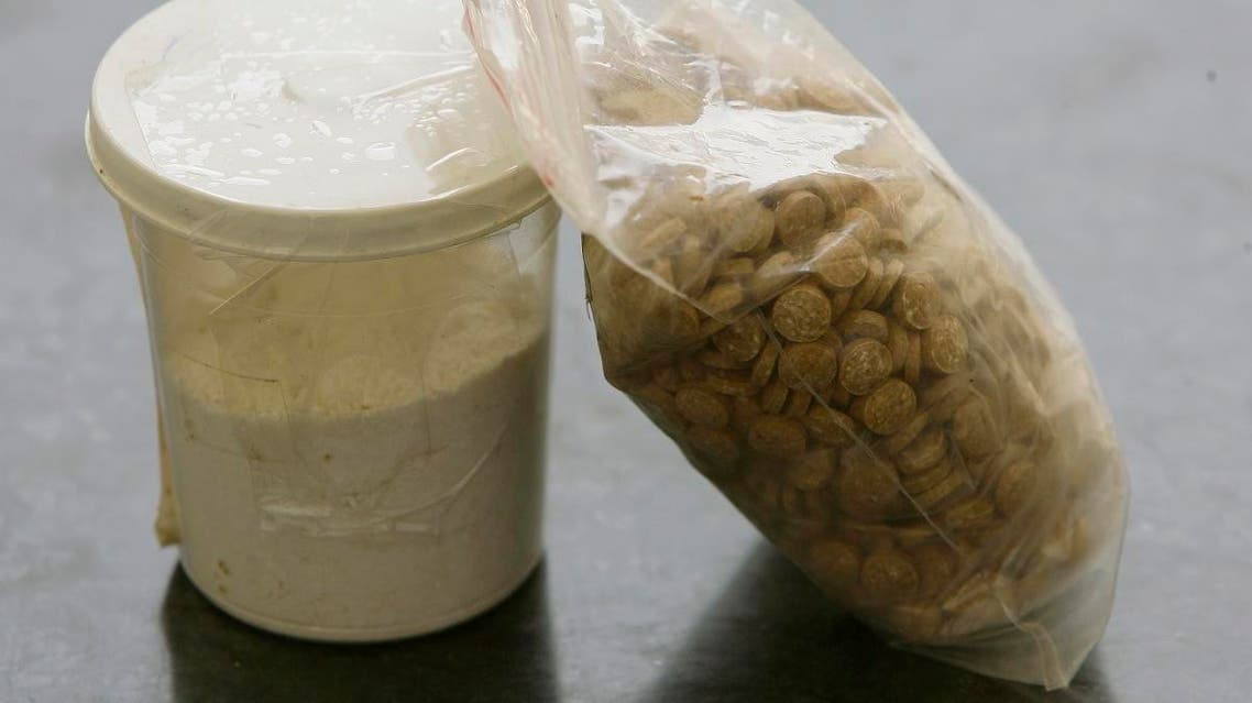 Captagon pills are displayed along with a cup of cocaine at an office of the Lebanese Internal Security Forces (ISF), Anti-Narcotics Division in Beirut on June 11, 2010. (AFP)
