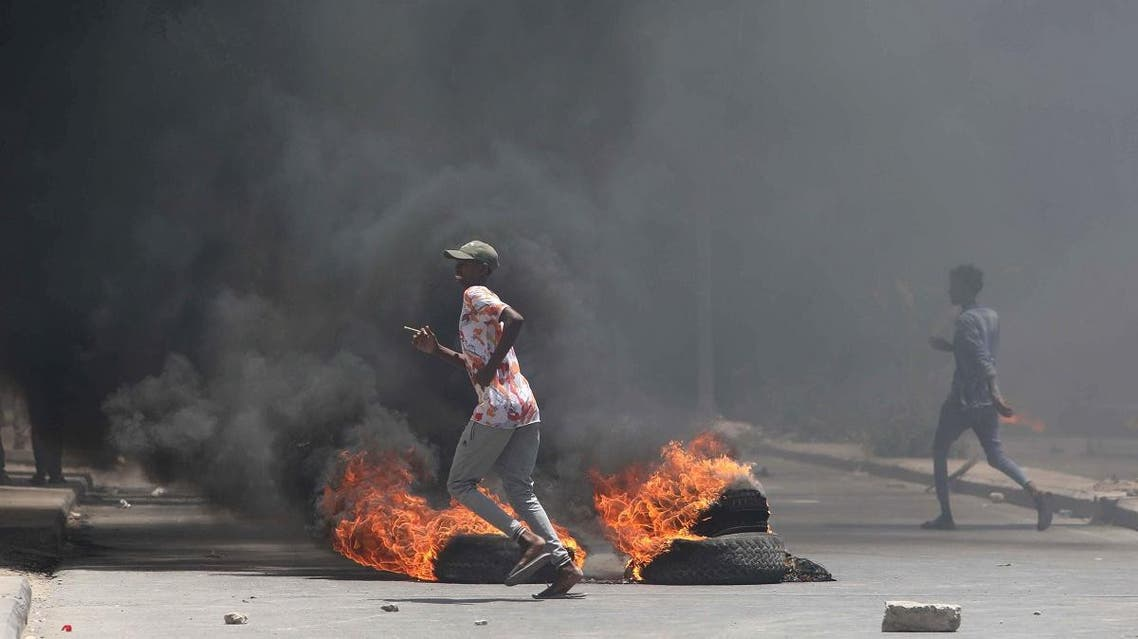 Somali demonstrators run past burning tires during a protest against Somali police in Mogadishu. (Reuters)