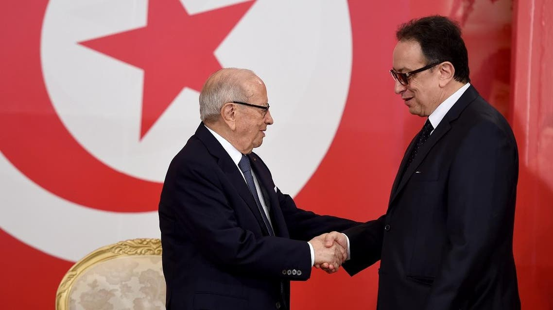 Tunisian President Beji Caid Essebsi (L) greets his son Hafedh Caid Essebsi, the general secretary of the Nidaa Tounes party. (AFP)