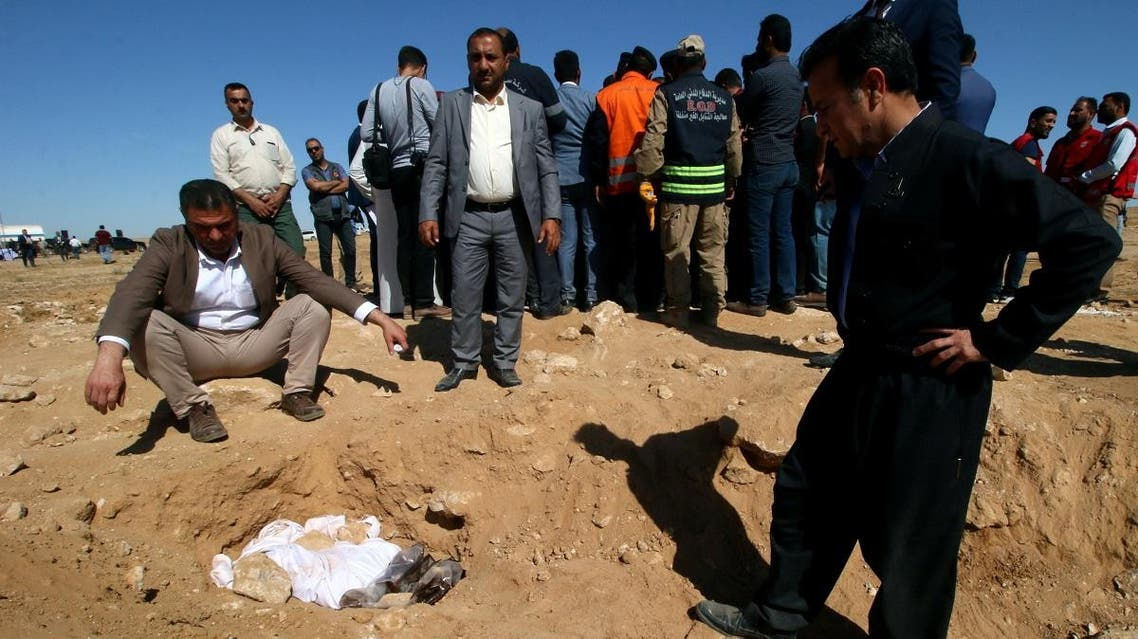 Kurdish men look at the covered bones from an unearthed mass grave of Kurds, west of the city of Samawa. (Reuters)