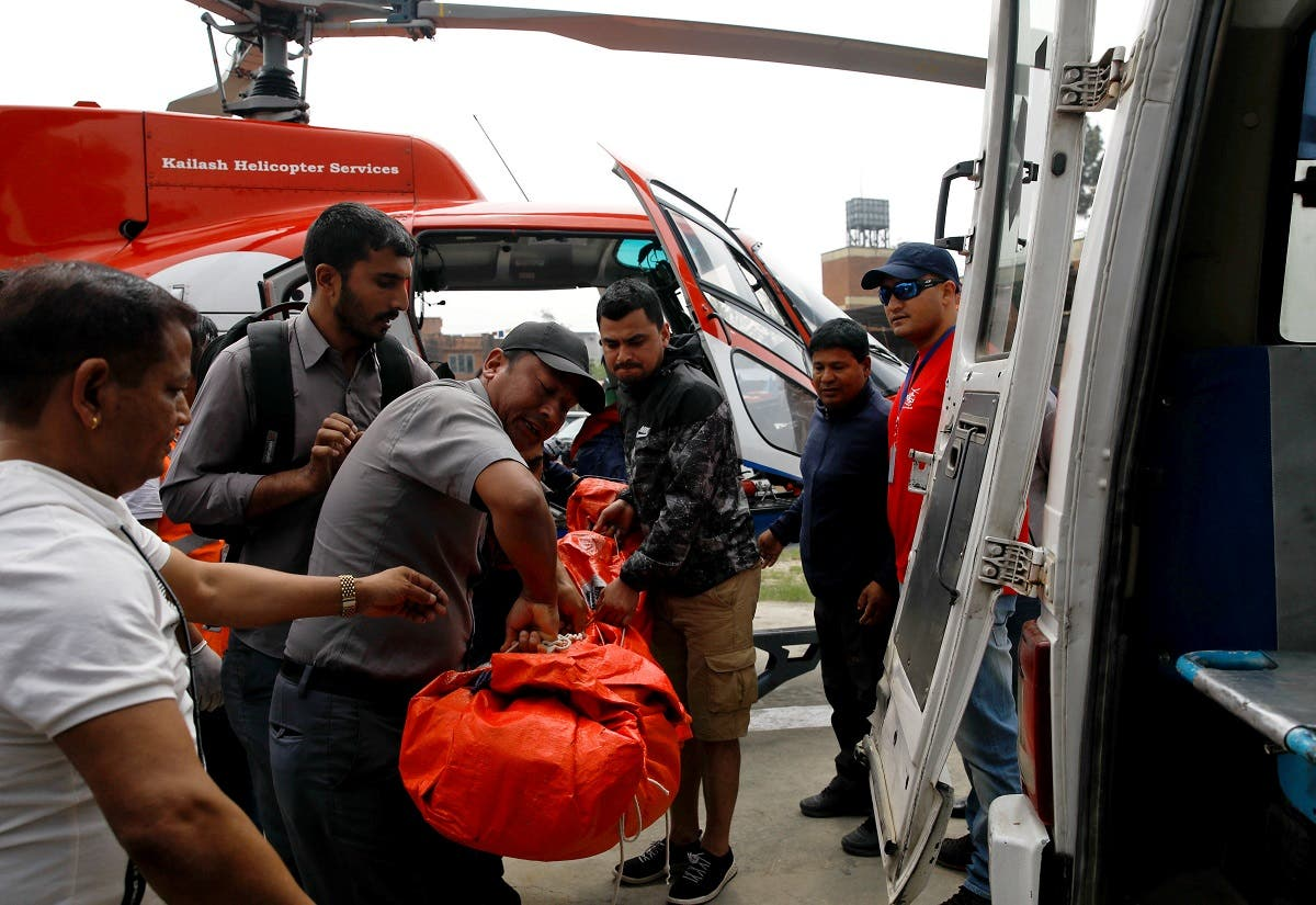 Officials carry a body of a victim of a small aircraft belonging to Summit Air, that crashed with a helicopter parked at Lukla airport, before it gets transported for postmortem examination at a hospital in Kathmandu Officials carry a body of a victim of a small aircraft belo. (Reuters)
