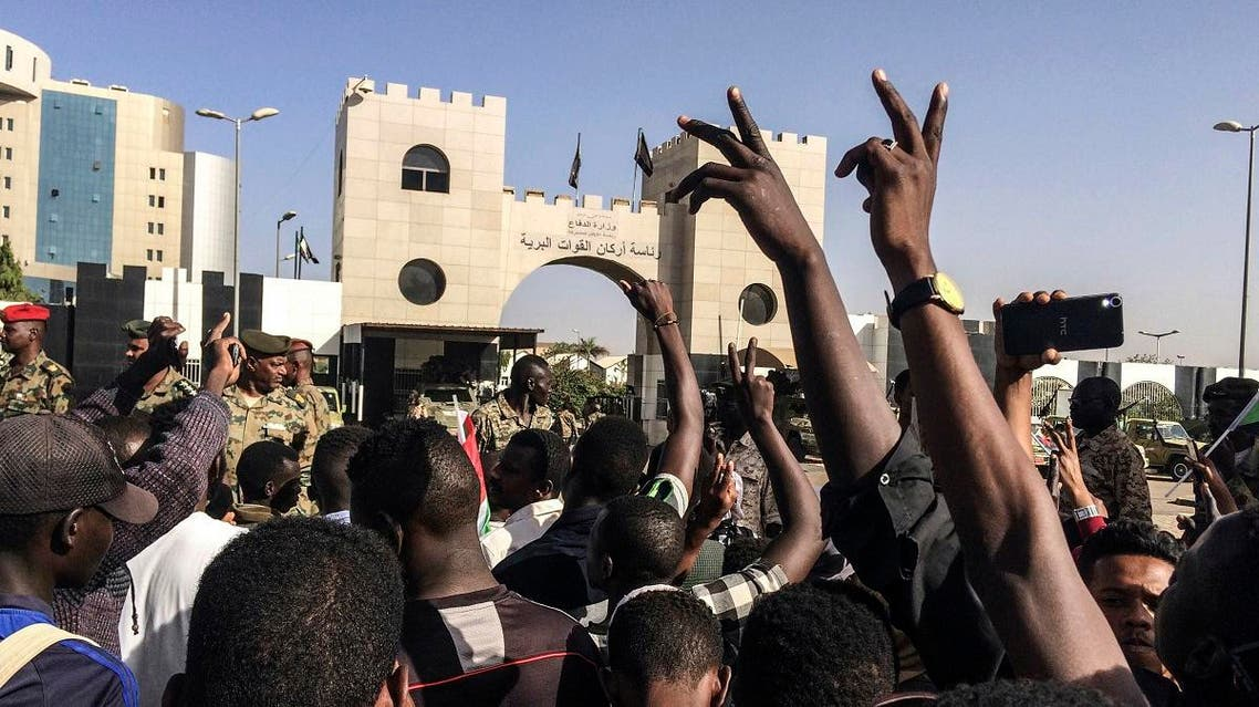 Sudanese demonstrators march with national flags as they gather during a rally demanding a civilian body to lead the transition to democracy, outside the army headquarters in the Sudanese capital Khartoum on Saturday, April 13, 2019. (AP)