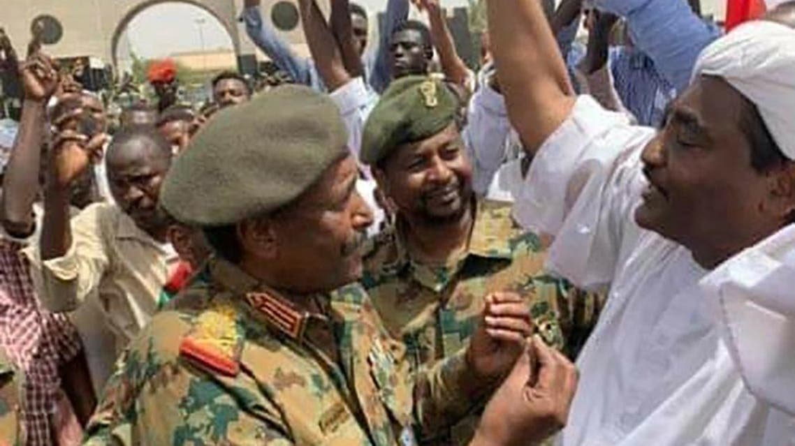 A photo of Lieutenant General Abdel Fattah al-Burhan, the new chief of the military council, went viral on social media, as he speaks with opposition figures demonstrating against Omar al-Bashir's regime, on April 12, 2019. (AFP)