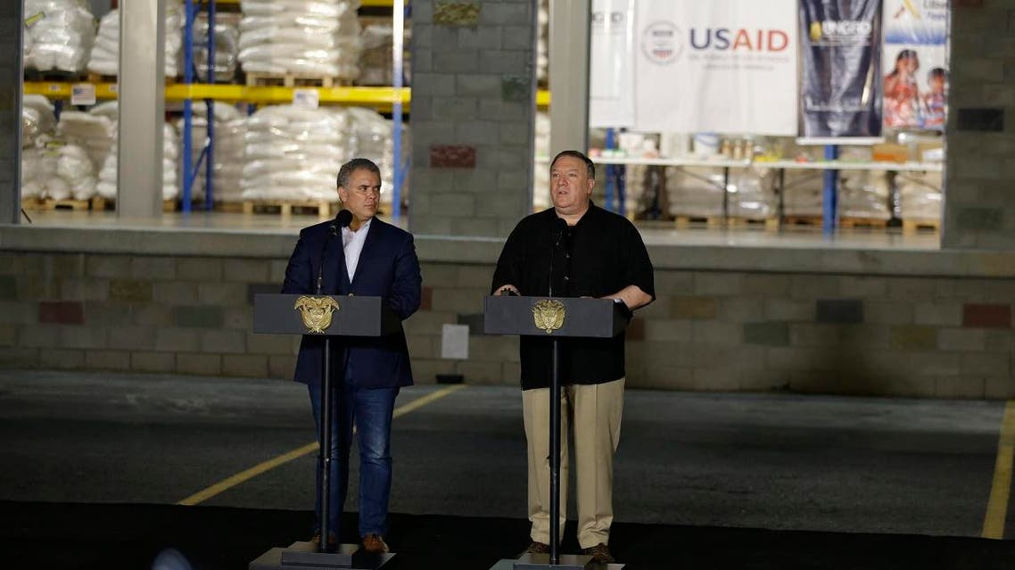 """U.S. Secretary of State Mike Pompeo, right, speaks next to Colombian President Ivan Duque as they give statements outside a warehouse that stores humanitarian aid for Venezuela, near the Tienditas International Bridge, coined """"Unity Bridge,"""" which connects Cucuta, Colombia with Tienditas, Venezuela, Sunday, April 14, 2019. (AP)"""