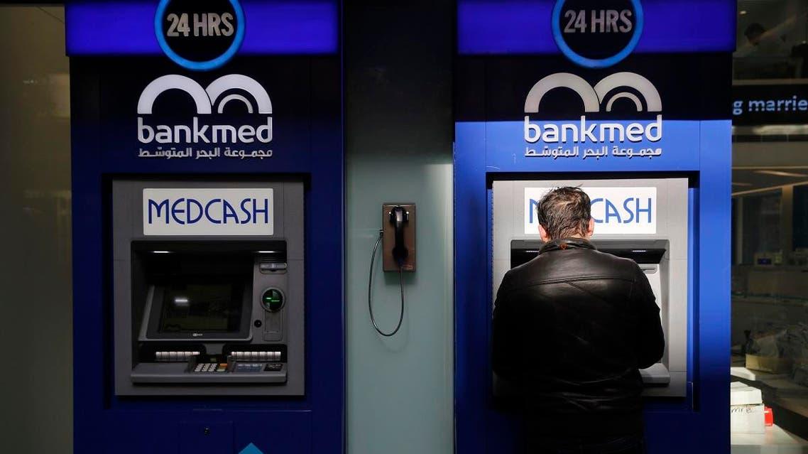 A man uses an ATM outside a bank, in Beirut, Lebanon, Tuesday, Jan. 22, 2019. (AP)