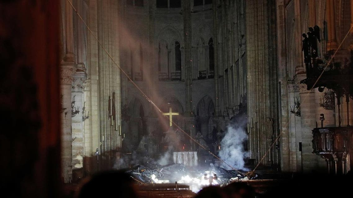 Smoke rises around the altar in front of the cross inside the Notre Dame Cathedral. (Reuters)