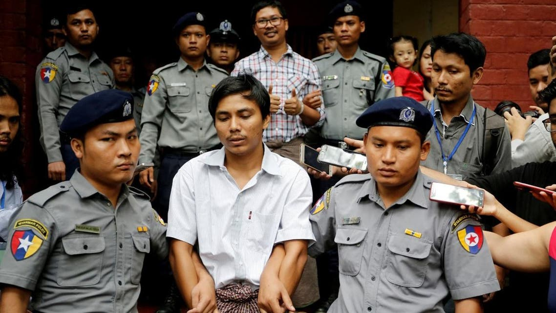 Detained Reuters journalist Kyaw Soe Oo and Wa Lone are escorted by police as they leave after a court hearing in Yangon,Myanmar, on August 20, 2018. (Reuters)