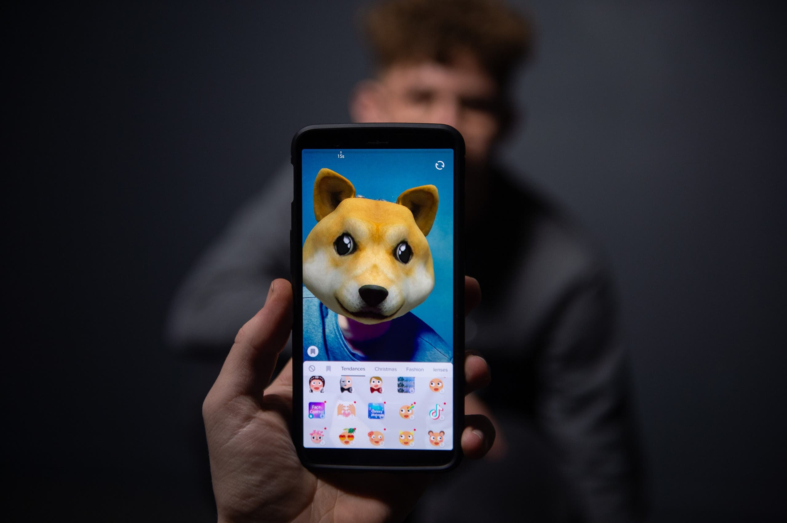 An AFP collaborator poses for a picture using the smart phone application TikTok in Paris on December 14, 2018. (AFP)
