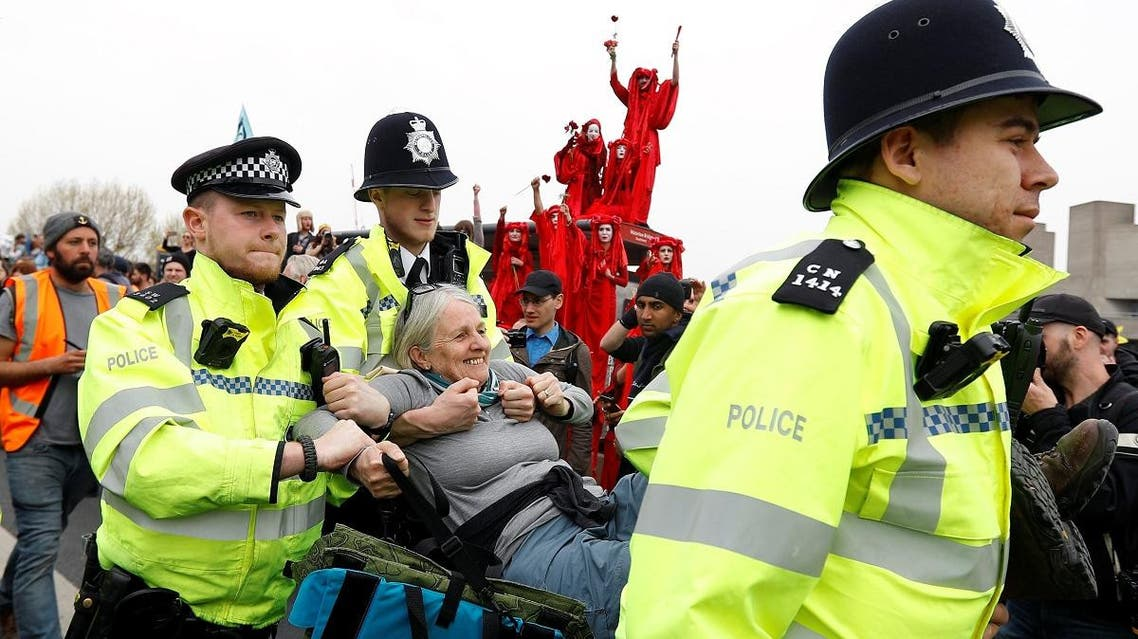 Police officers detain a climate change activist at Waterloo Bridge during the Extinction Rebellion protest in London on April 16, 2019. (Reuters)
