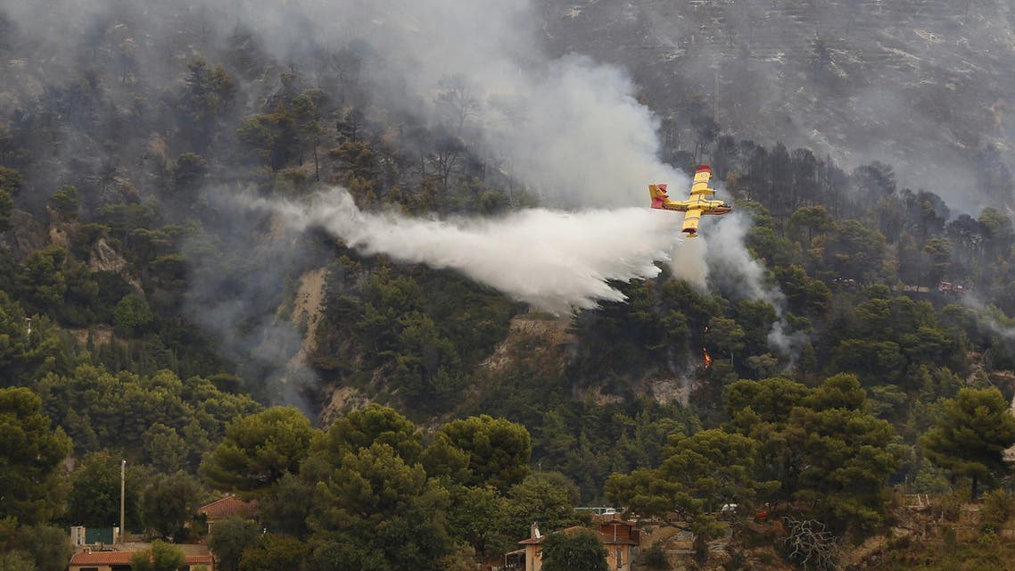 A fire-fighting plane drops water above a forest as a fire broke out at the French-Italian border in Menton, on September 9, 2015. (File photo: AFP)