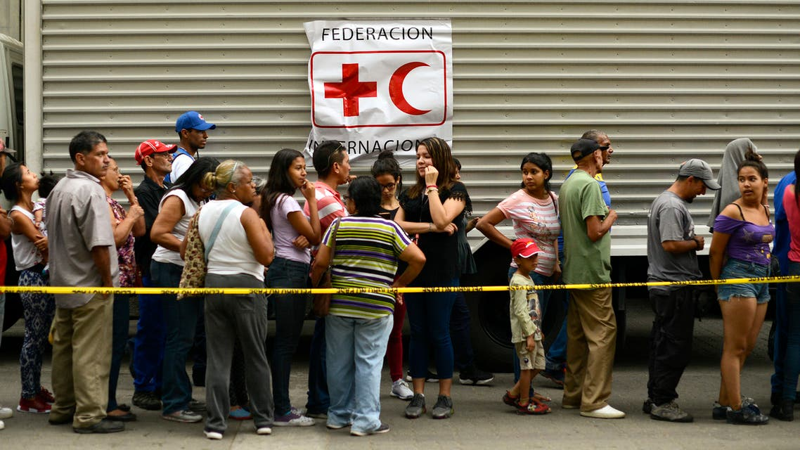 يصطف الناس للحصول على براميل لجمع أقراص تنقية المياه والمياه من أعضاء الصليب الأحمر الفنزويلي