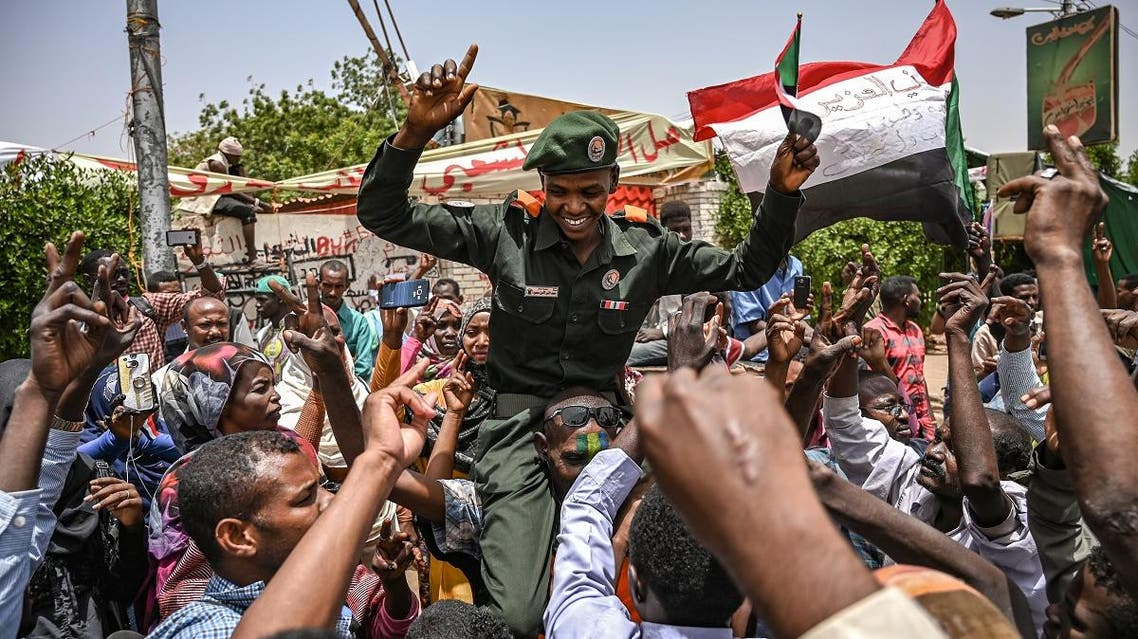 A Sudanese soldier joins protestors shouting slogans and waving national flags during a protest outside the army complex in the capital Khartoum on April 18, 2019. (AFP)