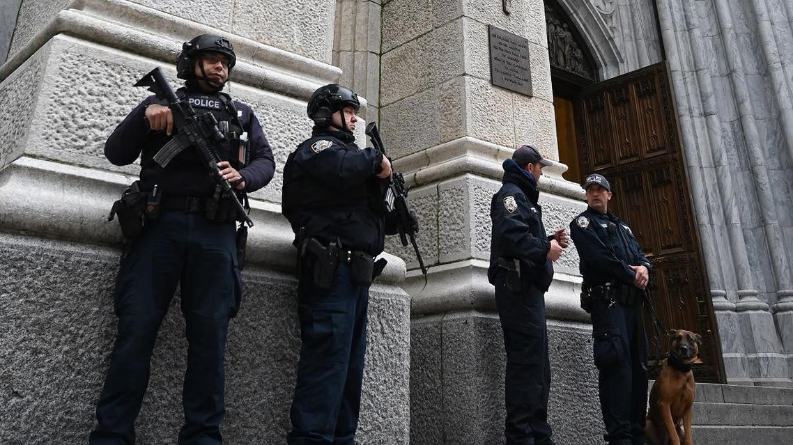 Members of the New York Police Department (NYPD) gather outside St. Patrick's Cathedral on 5th Avenue April 18, 2019, the morning after a man was arrested after trying to enter the Cathedral with gas cans