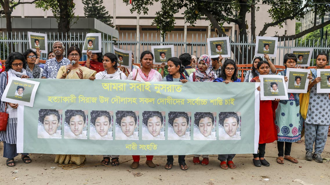 In this photo taken on April 12, 2019 Bangladeshi women hold placards and photographs of schoolgirl Nusrat Jahan Rafi at a protest in Dhaka, following her murder by being set on fire after she had reported a sexual assault. (AFP)