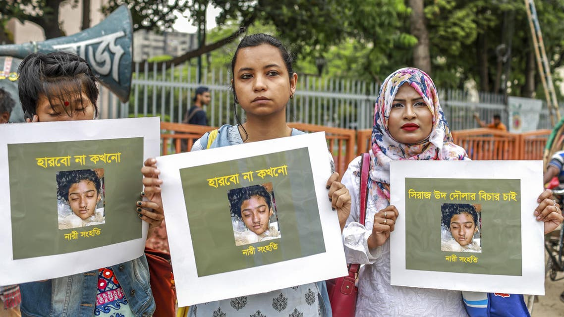 n this photo taken on April 12, 2019 Bangladeshi women hold placards and photographs of schoolgirl Nusrat Jahan Rafi at a protest in Dhaka, following her murder by being set on fire after she had reported a sexual assault.  (AFP)