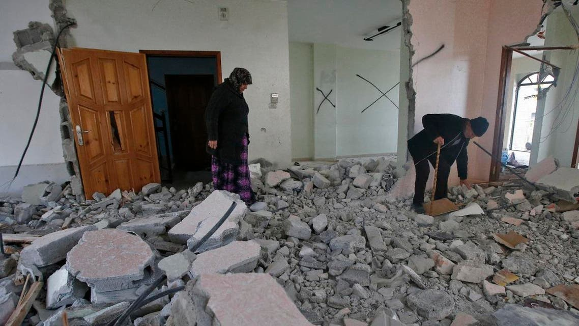 The parents of Arafat Irfaiya, a 29-year-old Palestinian-  stands inside the damaged family home after Israeli army buldoser destroyed it in the Israeli-occupied West Bank town of Hebron, on April 19, 2019. (AFP)
