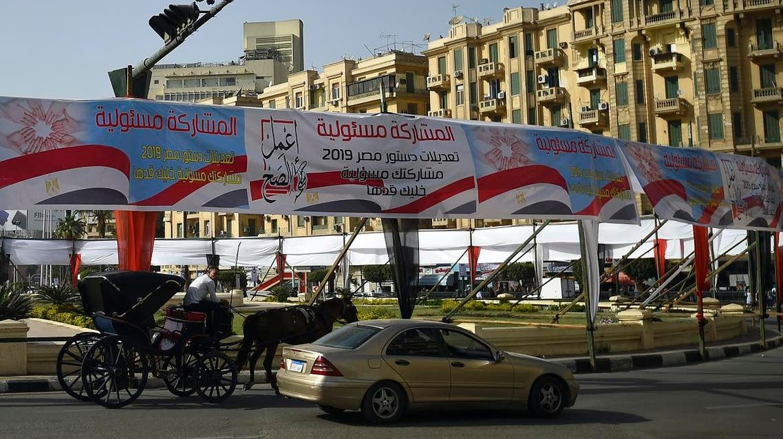 """Egyptians pass under banners reading in Arabic """"Do what is right"""", and """"Participation is your responsibility"""", urging voters to participate in the upcoming referendum for the constitutional amendments. (AFP)"""