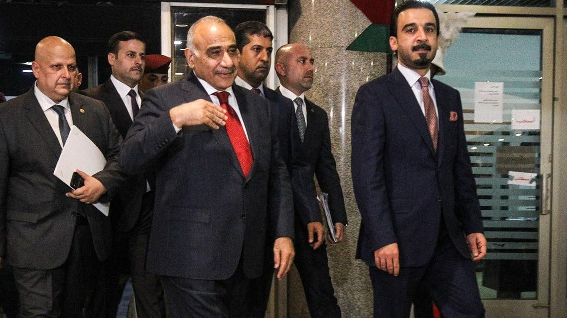 File photo of Iraq's prime minister Adel Abdel Mahdi (C-L) with parliament speaker Mohamhed Halbusi (R) at the parliament headquarters in the capital Baghdad. (AFP)