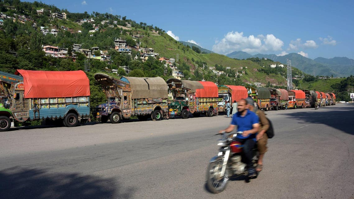 Trucks loaded with Indian goods are left parked on a road side after relatives of Pakistani Kashmiri truck drivers detained in Indian-held Kashmir on alleged drugs smuggling charges blocked the vehicles on the outskirts of Muzaffarabad, in Pakistani-administered Kashmir, on August 20, 2017. (AFP)