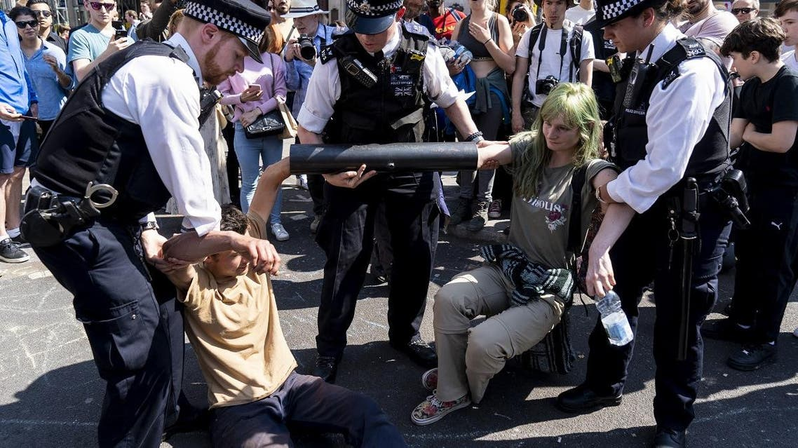 Police officers move climate change activists with their hands glued to a pipe as they continue to block the road at Oxford Circus in London. (AFP)