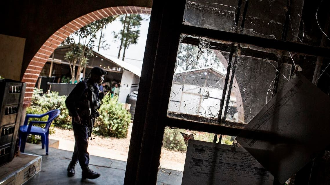 A Police officer stands guard next to a window riddled with bullet holes in an Ebola treatment centre, which was attacked in the early hours of the morning on March 9, 2019 in Butembo.