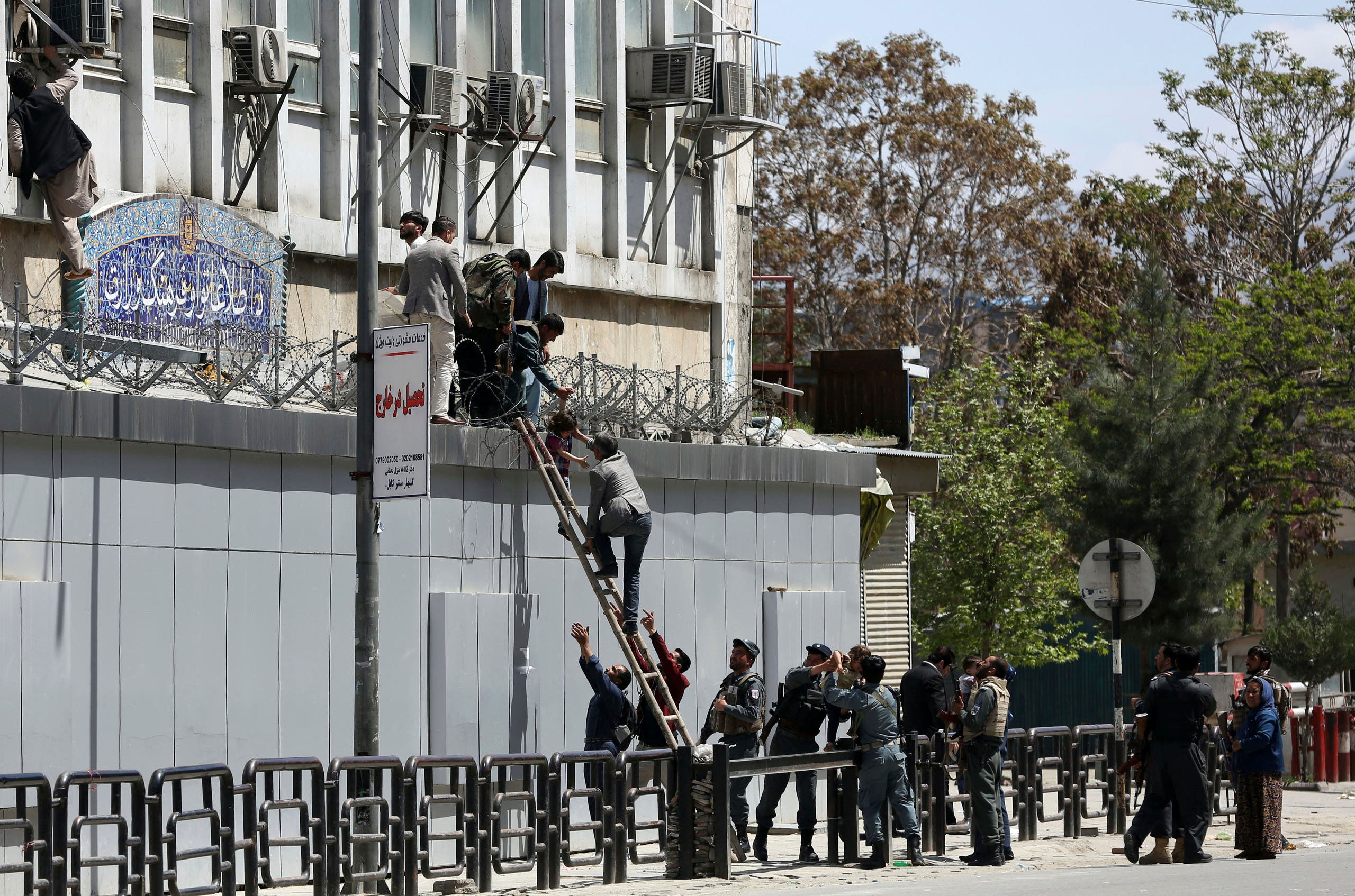 Security personnel rescue men from the information and culture ministry after an attack near the Telecommunication Ministry in Kabul, Afghanistan. (AP)