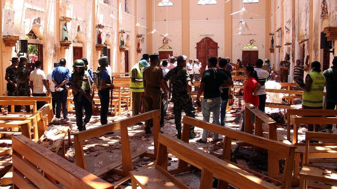 Sri Lankan security personnel walk through debris following an explosion in St Sebastian's Church in Negombo, north of the capital Colombo, on April 21, 2019. (AFP)