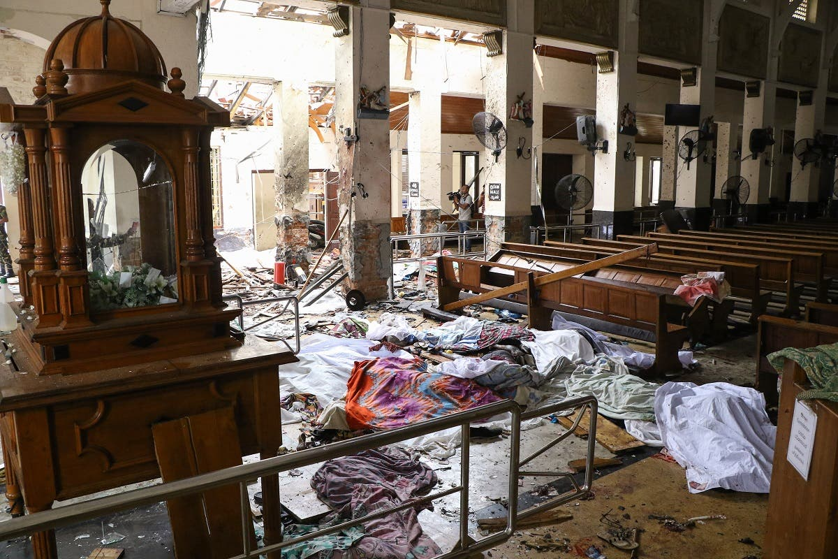 Sri Lankan security personnel walk past dead bodies covered with blankets amid blast debris at St. Anthony's Shrine. (AFP)