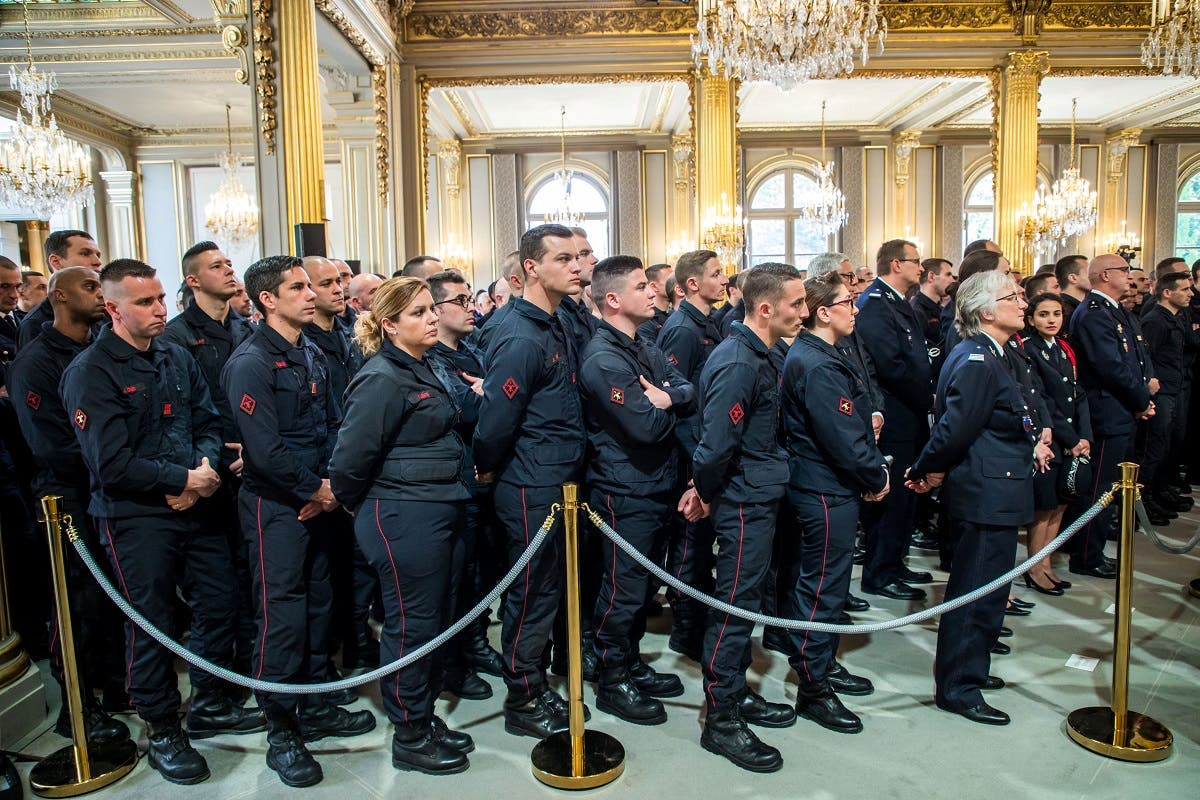 Firefighters' brigade and security forces listen to French President Emmanuel Macron's speech at Elysee Palace in Paris. (Reuters)