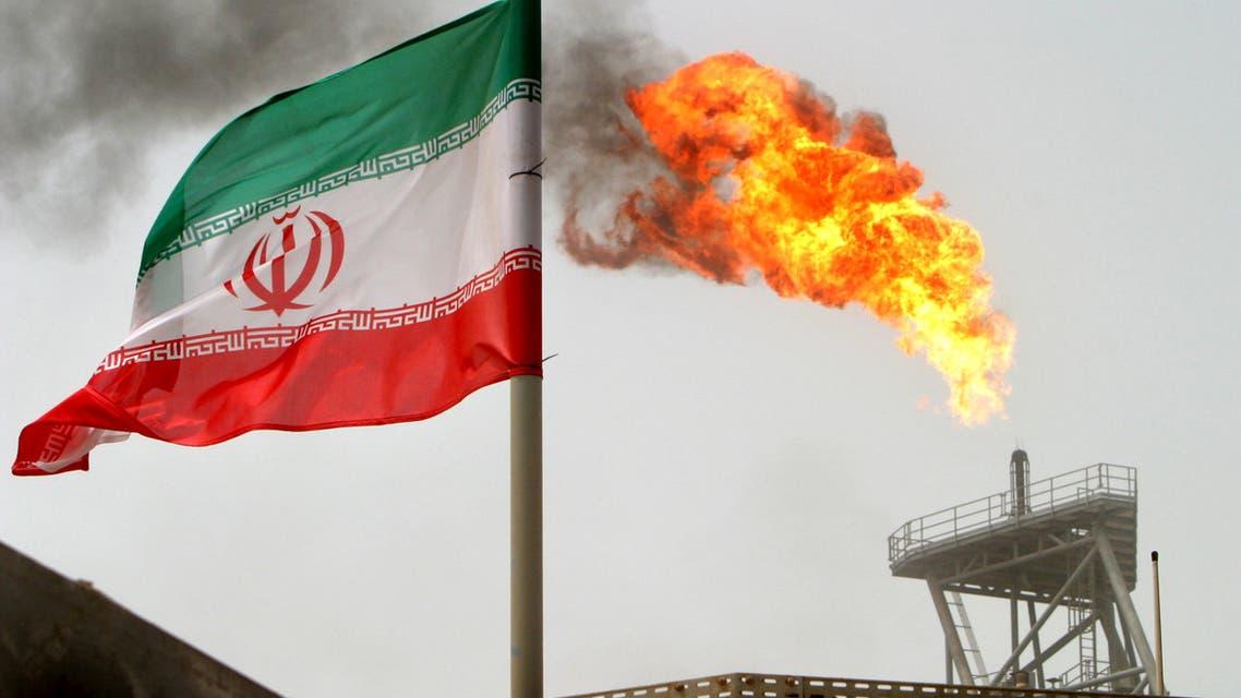 غاز يحترق فوق منصة لإنتاج النفط في حقول نفط سوروش بجوار العلم الإيراني