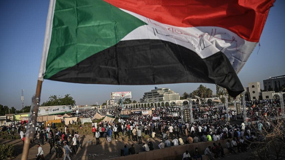 Sudanese protesters gather as they wave national flags during a protest outside the army headquarters in the capital Khartoum on April 21, 2019. (AFP)